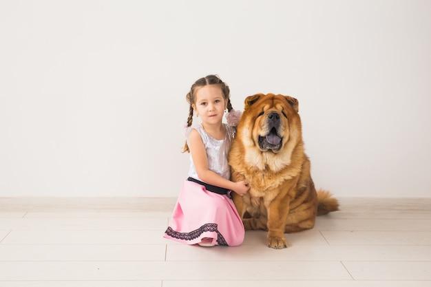 Haustiere, kinder und freundschaftskonzept - kleines mädchen, das ihren hund chow-chow über weißem hintergrund umarmt