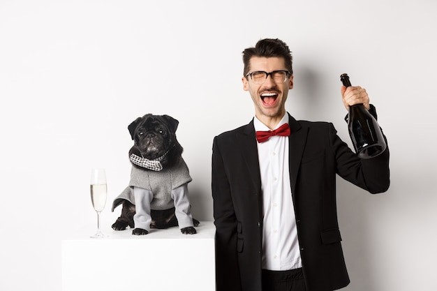 Haustiere, winterferien und neujahrskonzept. glücklicher mann, der weihnachtsfeierhaustier feiert, mit niedlichem hund im kostüm stehend, champagner trinkend und sich freuend, weiß.