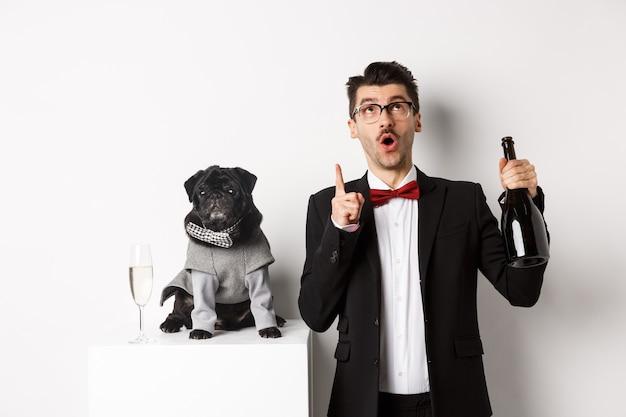 Haustiere, winterferien und neujahrskonzept. hübscher junger mann im anzug, der weihnachten mit schwarzem hund, welpe trägt kostüm feiert, besitzer, der auf kopienraum schaut und zeigt.