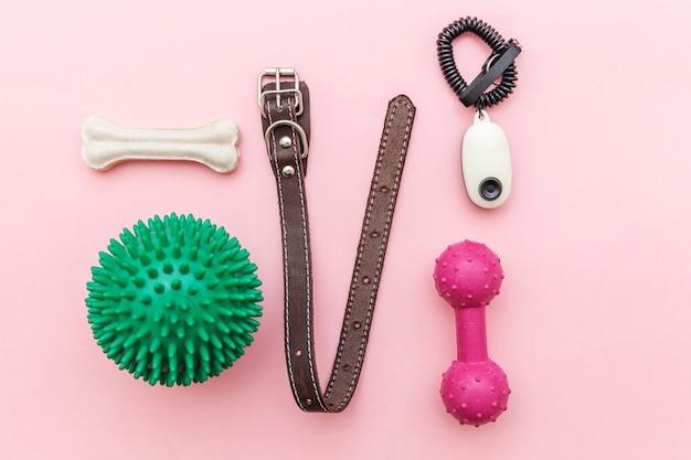 Haustierpflege- und tierkonzept. spielzeug und zubehör für das spielen und trainieren des hundes lokalisiert auf rosa pastelltrendhintergrund