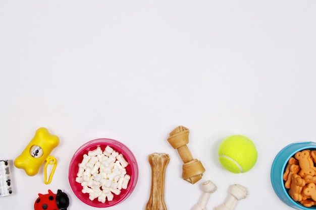 Haustierzubehör, -nahrung und -spielzeug auf weißem hintergrund. flach legen. draufsicht.