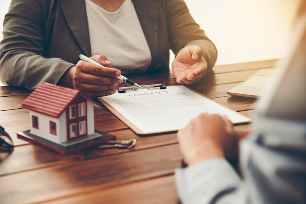 Hausunterzeichner, die das unterschriftsdarlehensdokument für das wohneigentum mit dem eigentum von immobilienmaklern unterzeichnen hypotheken- und immobilieninvestition, hausratversicherung