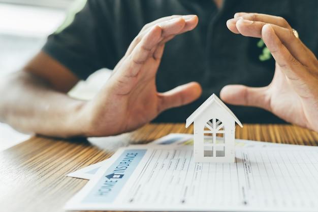 Hausversicherung oder objektschutz. versicherungsvertreter komplett, hölzernes musterhaus auf dem geld.