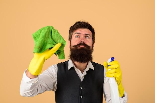 Hauswirtschafts- und menschenkonzeptmann in gummihandschuhen mit lappen und sprühmann von