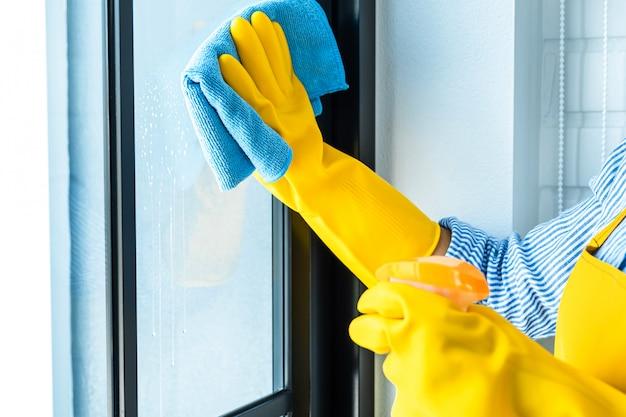 Hauswirtschafts- und reinigungskonzept der frau, glückliche junge frau, die staub mit einem spray und einem staubtuch abwischt, während in glas zu hause gereinigt wird