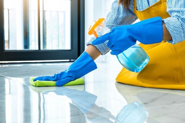Hauswirtschafts- und reinigungskonzept der frau, glückliche junge frau in den blauen gummihandschuhen, die staub mit einem spray und einem staubtuch abwischen, während auf dem boden zu hause gereinigt wird