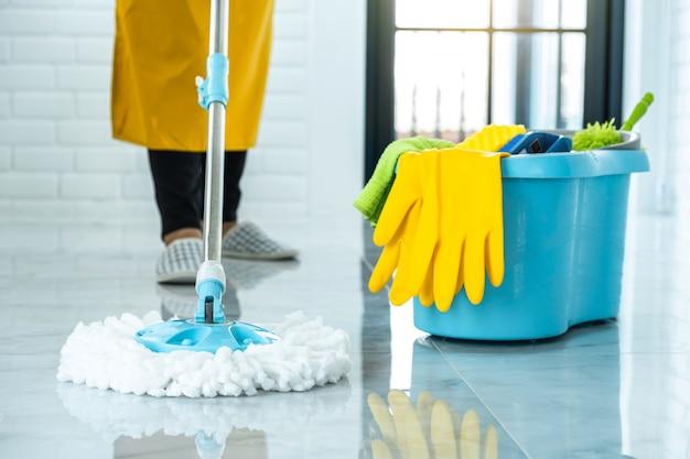Hauswirtschafts- und reinigungskonzept der frau, glückliche junge frau in den blauen gummihandschuhen, die staub mit mopp abwischen, während sie auf boden zu hause reinigen