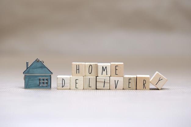 Hauszustellungstext mit holzwürfeln und kleinem miniaturhaus auf unscharfem hintergrund, geschäft, bleiben sie zu hause für covid-19, wir liefern konzepthintergrundkopierraum
