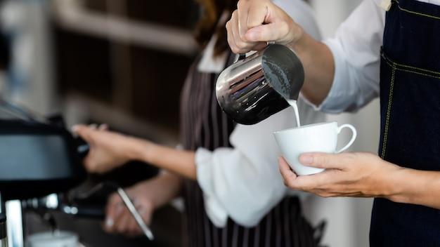 Hautnah hamd. junge asiatische mann gießt milch in kaffee espresso zubereiten. professioneller barista, der kaffee auf der theke zubereitet. barista macht cappuccino, barkeeper bereitet kaffeegetränk zu.