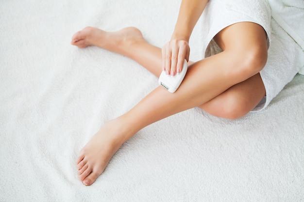 Hautpflege. frau, die ihre beine im badezimmer rasiert