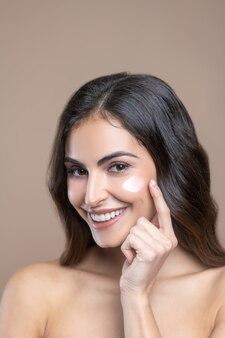 Hautpflege. freudige süße langhaarige frau mit nackten schultern und creme auf der wange, die den finger zu ihrem gesicht berührt