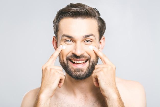 Hautpflege. hübscher glücklicher junger hemdloser mann, der creme auf sein gesicht aufträgt und sich mit lächeln betrachtet, während er über grauem hintergrund steht