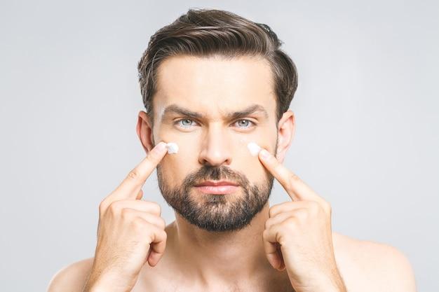 Hautpflege. hübscher junger hemdloser mann, der creme an seinem gesicht anwendet und kamera betrachtet, während über grauem hintergrund steht