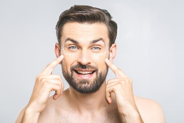 Hautpflege. hübscher junger hemdloser mann, der creme an seinem gesicht anwendet und kamera betrachtet, während über grauem hintergrund steht Premium Fotos