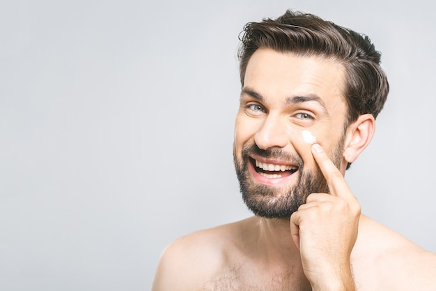 Hautpflege. hübscher junger hemdloser mann, der creme an seinem gesicht anwendet und kamera mit lächeln betrachtet, während er über grauem hintergrund steht