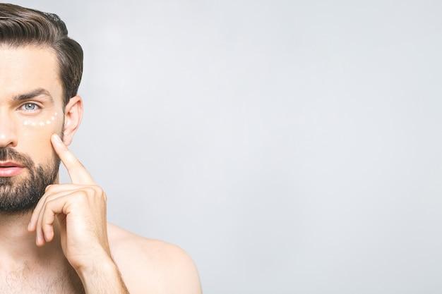 Hautpflege. hübscher junger hemdloser mann, der creme an seinem gesicht anwendet und sich betrachtet, während er über grauem hintergrund steht
