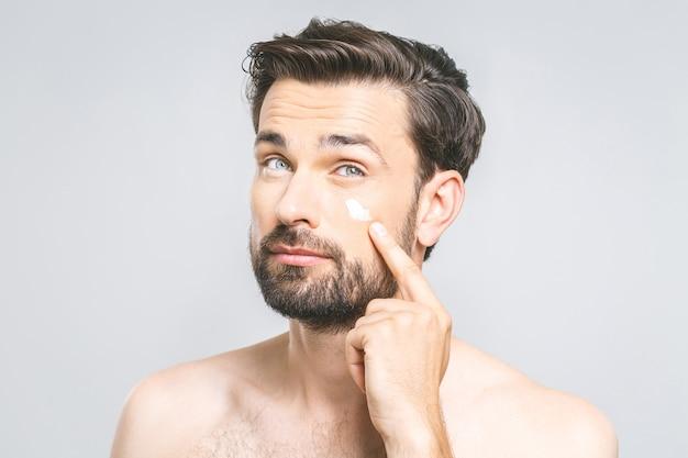 Hautpflege. hübscher junger hemdloser mann, der creme an seinem gesicht anwendet und sich mit lächeln betrachtet, während er über grauem hintergrund steht Premium Fotos