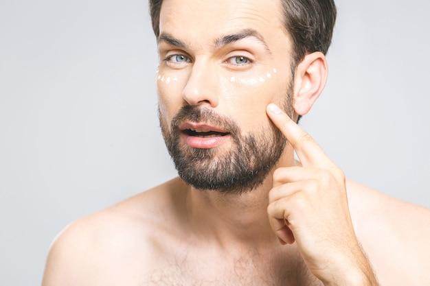 Hautpflege. hübscher junger hemdloser mann, der creme an seinem gesicht anwendet und sich mit lächeln betrachtet, während er über grauem hintergrund steht