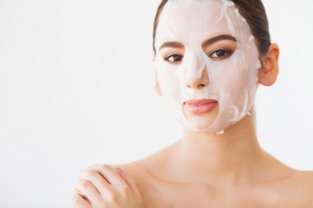 Hautpflege. junge frau, die maske von der gesichtshaut entfernt. frauen-schönheits-gesicht