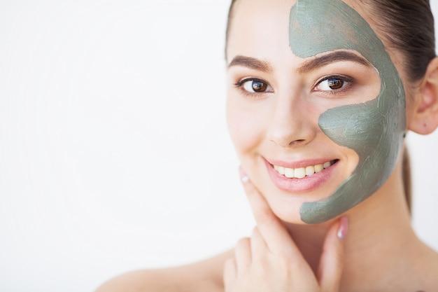 Hautpflege. junge frau mit kosmetischer lehmmaske, die gurke an ihrem badezimmer hält
