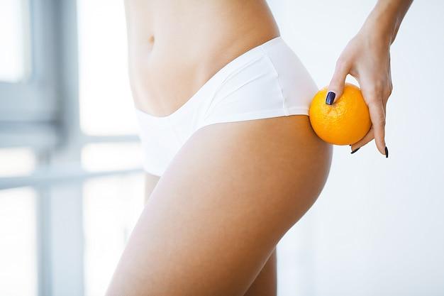 Hautpflege-kontrolle. frau, die eine orange gegen ihre schenkel hält