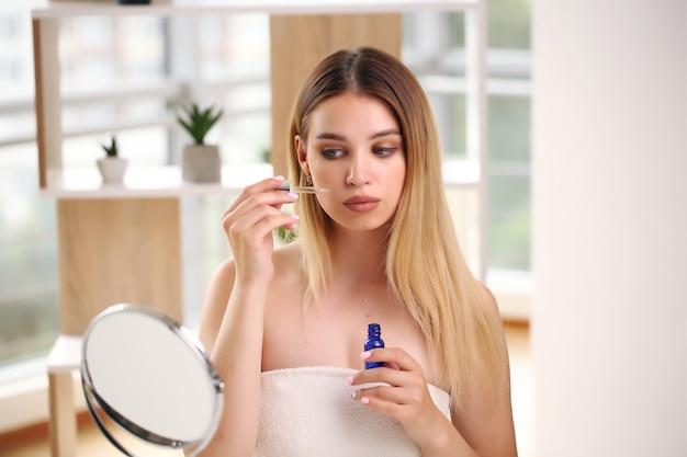Hautpflege-konzeptporträt der glücklichen frau, die kosmetik anwendet.