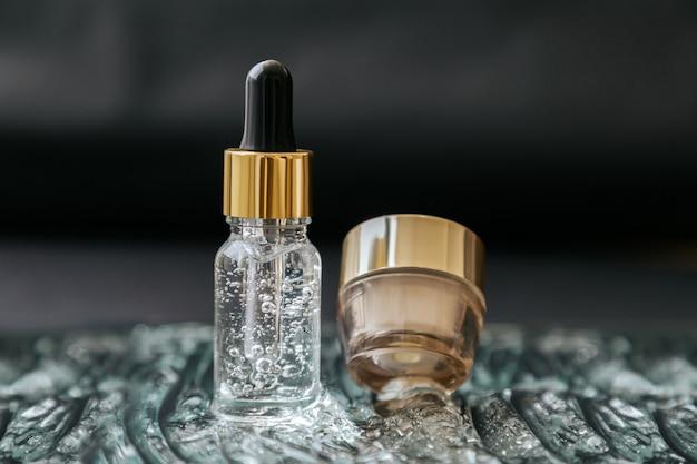 Hautpflege-kosmetik-serumflasche mit flüssiger kollagen-hyaluronsäure und feuchtigkeitscreme-glas auf wassergelblasen-texturoberfläche. luxusgold beauty wasserbalance kosmetik auf schwarzem hintergrund.