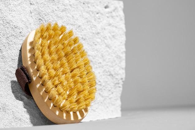 Hautpflege-massagebürste auf grauem betonblock nah oben