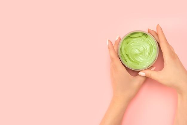 Hautpflege mit naturkosmetik. frauenhände halten ein glas naturkosmetik. creme. öko-kosmetik. creme in die hände. hautpflege. platz kopieren. rosa hintergrund