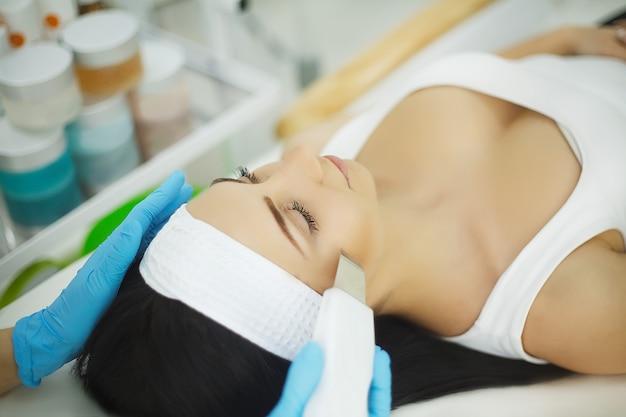 Hautpflege. nahaufnahme der schönheit ultraschall-hohlraumbildungs-gesichtsschale empfangend. ultraschall-hautreinigungsverfahren. schönheitsbehandlung. kosmetologie. beauty spa salon.