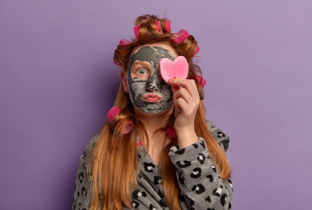 Hautpflege routine. kleines ingwer-mädchen trägt lockenwickler, trägt eine pflegende gesichtsmaske aus ton für glatte haut auf, bedeckt das auge mit einem kosmetischen schwamm, trägt ein kleid und führt zu hause schönheitsbehandlungen durch.
