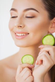 Hautpflege. schöne junge frau mit gurken auf augen