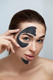 Hautpflege. schönes frauengesicht mit kosmetischer spa-tonmasken-nahaufnahme. mädchenmodell mit schwarzer feuchtigkeitsmaske, die schönheits-spa-behandlung tut.