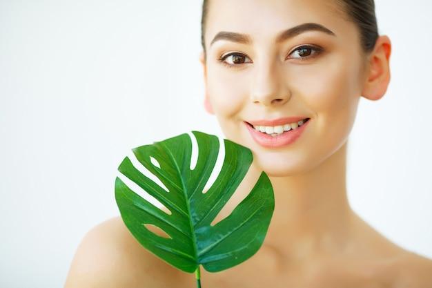 Hautpflege, schönes gesicht der jungen frau mit blume