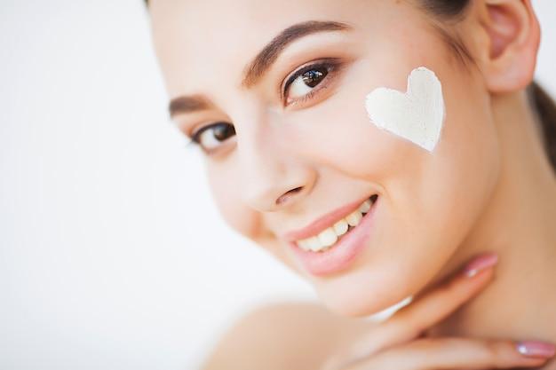 Hautpflege. schönes modell, das kosmetische cremebehandlung auf ihrem gesicht aufträgt