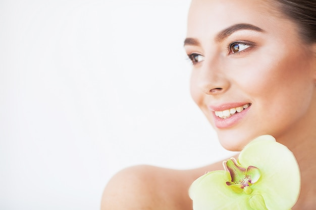 Hautpflege. schönes vorbildliches woman with perfect skin und orchid flower near her face