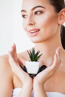 Hautpflege. schönheits-frauen-gesicht mit gesunder haut und grünpflanze