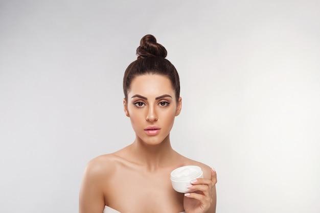Hautpflege. schönheitskonzept. junge frau, die kosmetische feuchtigkeitscreme hält