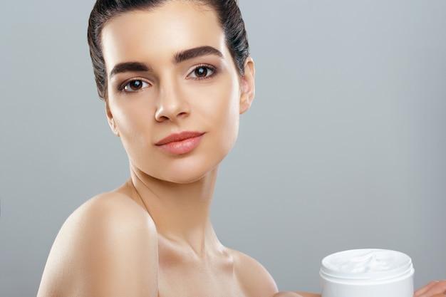 Hautpflege. schönheitskonzept. junge hübsche frau, die kosmetische creme hält. schönheitskonzept.