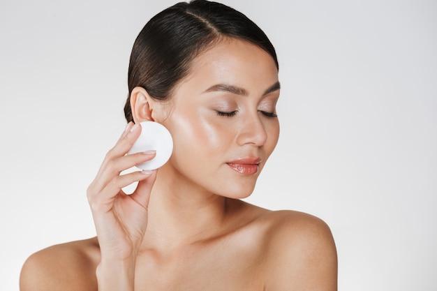 Hautpflege und gesunde behandlung der frau make-up vom gesicht mit der baumwollauflage entfernend, lokalisiert auf weiß
