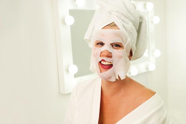 Hautpflege- und schönheitskonzept feuchtigkeitsmaske anti-aging-verfahren frau, die blattmaske auf ihre... Premium Fotos
