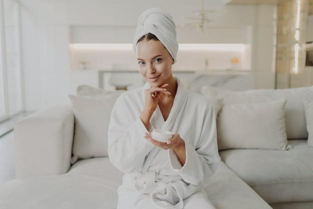 Hautpflege- und schönheitskonzept. porträt einer jungen attraktiven frau in bademantel und handtuch auf dem kopf, die ein sahneglas hält und lächelt, während sie auf dem sofa im wohnzimmer sitzt und kosmetische eingriffe macht