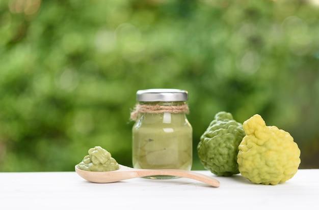 Hautpflege- und spa-konzept, thailändischer stil mit frischer und flüssiger bergamotte in flasche und holzlöffel auf weißem holztisch mit grünem naturhintergrund