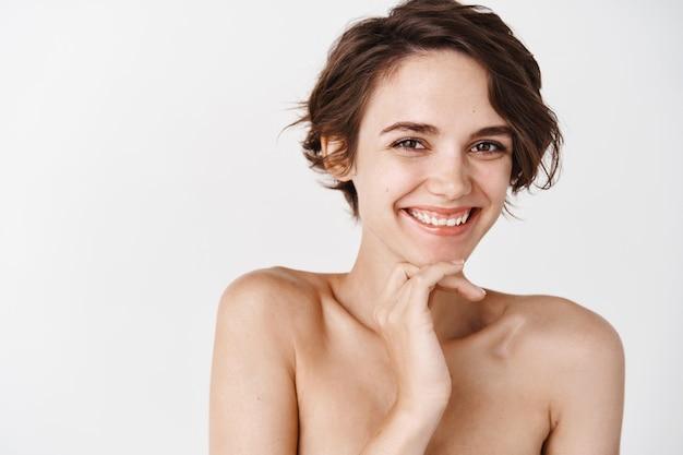 Hautpflege und tägliche pflege. lächelnde frau mit nackten schultern lächelnd und kichernd, stehend auf weißer wand. konzept der gesichtspflege