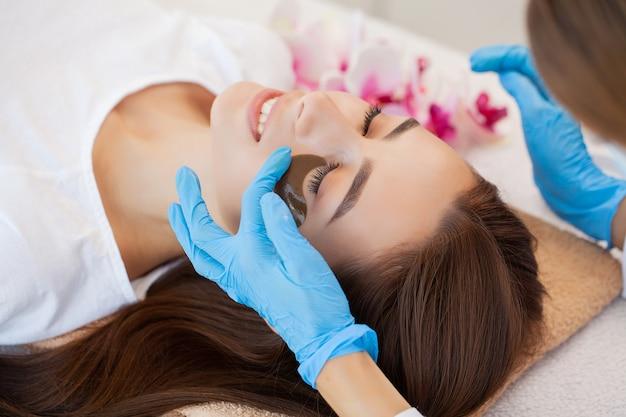 Hautpflege unter den augen, flecken werden auf die junge frau aufgetragen.