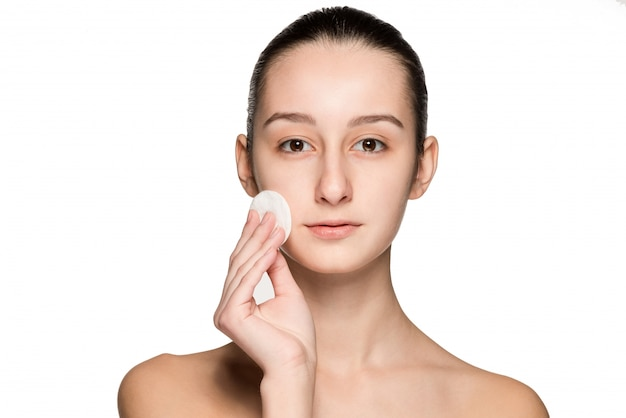 Hautpflegefrau, die gesicht mit wattestäbchenauflage entfernt