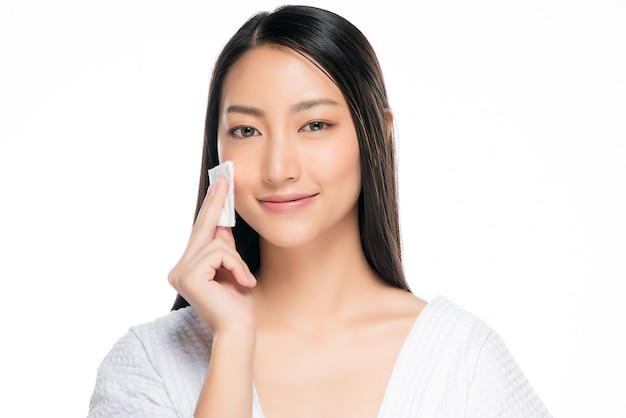 Hautpflegefrau, die gesichtsmake-up mit wattestäbchenauflage entfernt.