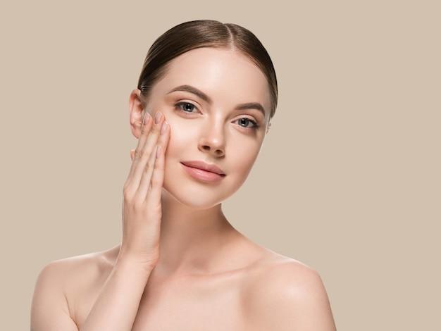 Hautpflegefrau mit den händen porträthautnahaufnahme kosmetisches alterskonzept. hintergrundfarbe braun