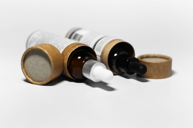 Hautpflegekonzept. ätherisches öl in pipettenflaschen, kartons in form eines zylinders. hintergrund des weißen studiohintergrunds.