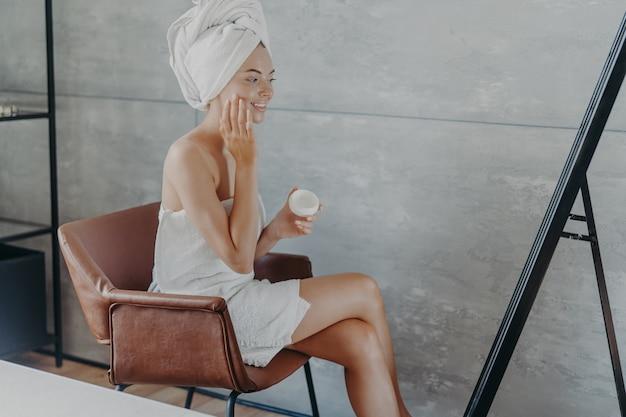 Hautpflegekonzept. innenaufnahme der hübschen lächelnden frau sitzt im bequemen sessel gegenüber spiegel
